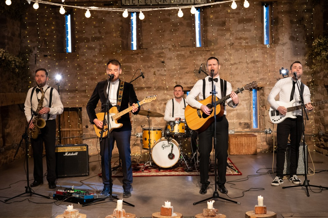 Band performing with string lights in background