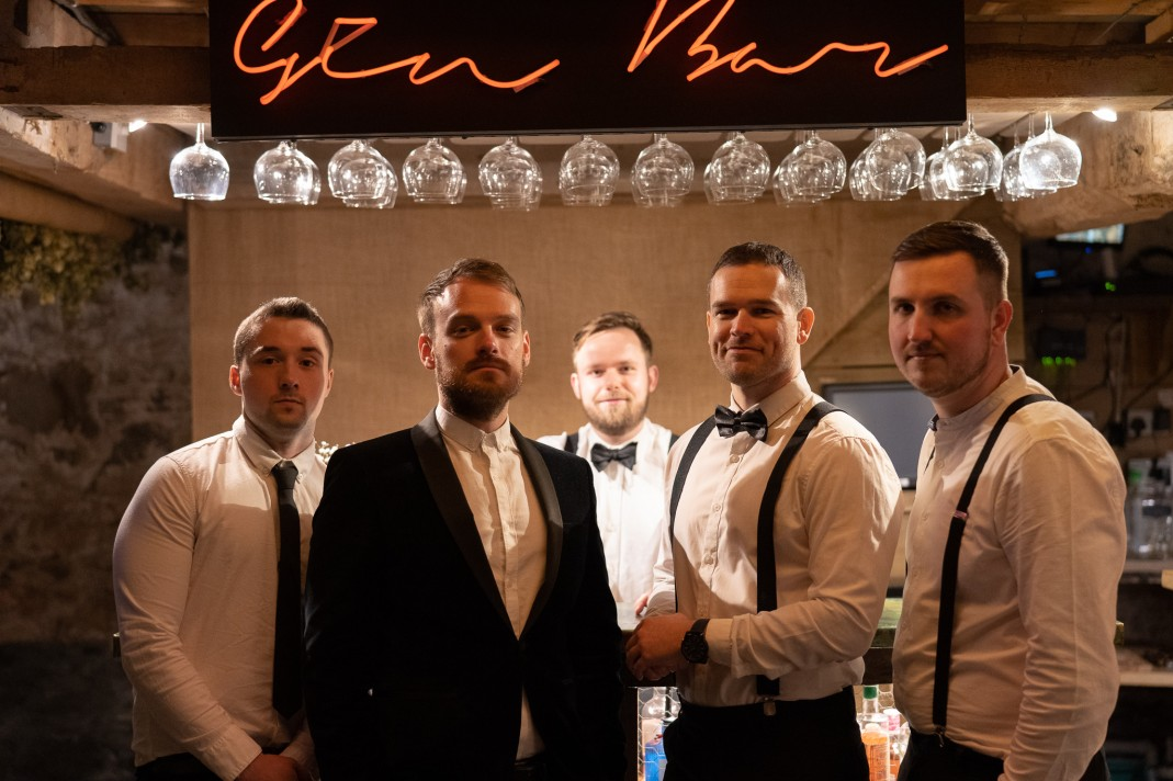 The band posing in front of a bar