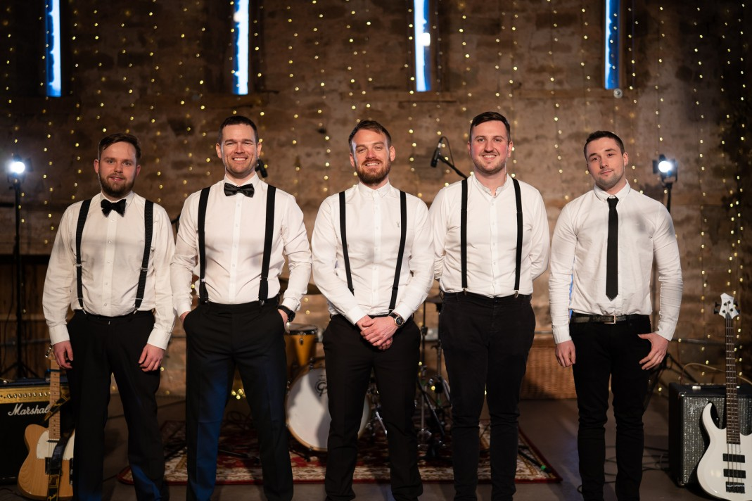 The band posing together in front of fairy lights