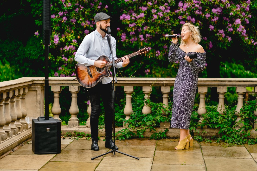 Acoustic duo with guitar and female singer outside on a patio