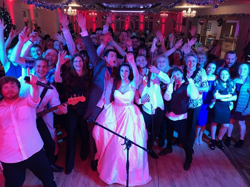 Wedding party posing on dancefloor with the wedding band